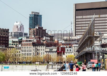 Montreal Canada - May 12 2016: Montreal downtown from Old Port docks with tourists wlaking around.