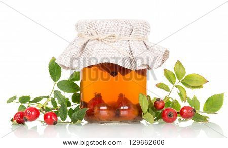 Tincture of rose hips and fresh berries isolated on white background