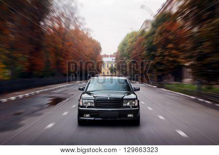 Saratov, Russia - September 28, 2014: Black car Mercedes-Benz speed drive on asphalt road in city at daytime