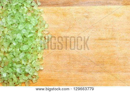Green sea salt on the wooden background