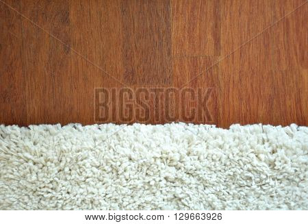 Decorative white fur carpet on wood floor background