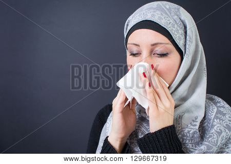 Beautiful muslim woman having a flue and sneezing