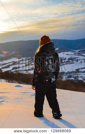 Mountain top at sunset. Girl gazing into the distance. Contemplation of sunset