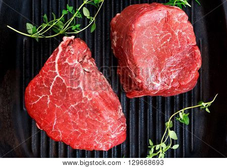 Fresh close up Raw Beef steak Mignon with thyme on grilled pan.