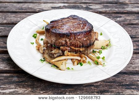 Tasty Beef Mignon steak with mushrooms and herbs on plate
