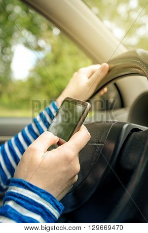 Woman driving car and reading received sms message on smartphone using mobile phone in traffic.