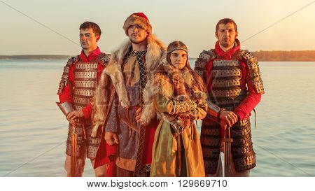 North Prince With The Princess And Two Warriors With Swords On The River Background.