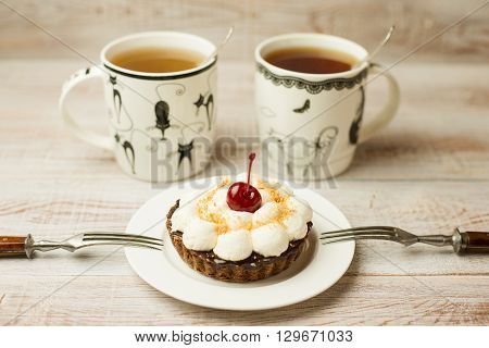 Two Cup of tea and cake with a cherry on the table