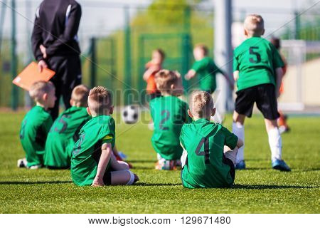 Youth soccer team together watching football game. Soccer tournament for young players. Boys sitting on a sports field and supporting team.