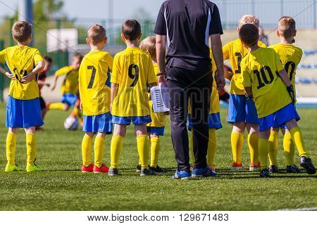 Coach and youth soccer reserve players watching football match. Coach giving young soccer team instructions. Coach briefing. Soccer football background.