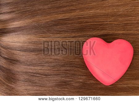 Red heart on a background of long, well-groomed hair brown