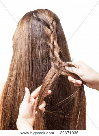 Hands masters weave braid of four parts with long smooth hair isolated on white