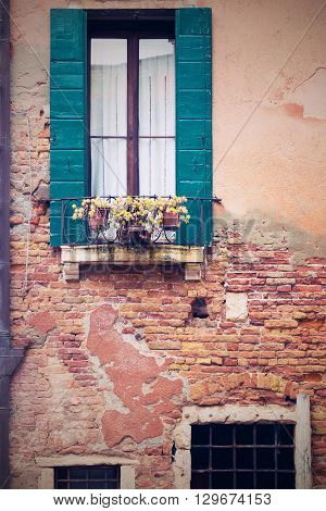 the old destroyed brick facade of the ancient house with a window and flowers in a cachepot on a window sill