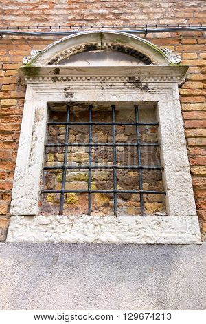 old brick facade of the ancient building with a window and a lattice in retro style