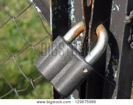 Old rusty padlock on metal mesh-netting fence with door with flaked paint