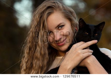 poster of Beautiful, attractive, nice, pretty girl with long, curly, wavy hair hug nice cat, black cat, lovely cat with green eyes, mysterious cat. Pretty, cheerful, smiling, happy girl with cat, girl hold cat in hands, cat.