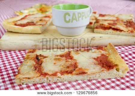 handcraft margherita pizza with near a cup of cappuccino