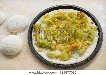 balls of pizza dough nearby at zucchini flowers pizza in a a baking tray