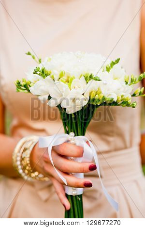 Wedding bouquet with white freesias closeup in bride's hands