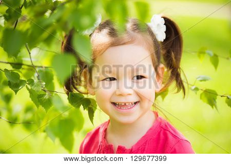 Close Up Of Face Of Child Playing Hide And Seek Outdoors In Park