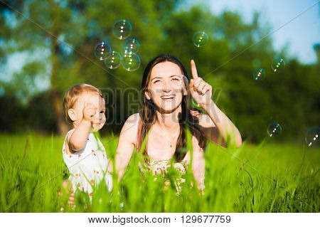 Mom And Little Daughter Cheerfully Catching Soap Bubbles