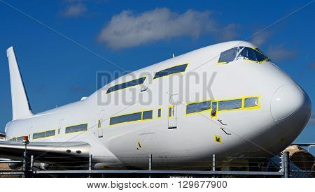 Jumbo plane sits on the tarmac behind a fence during the finishing process.