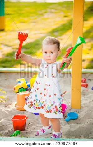 Little Child Playing With Toys In Sand On Children Playground