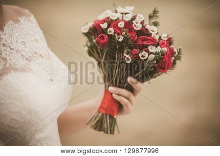 Beautiful Wedding Bouquet Of Red Roses Flowers In Hand Of Anonymous Young Bride