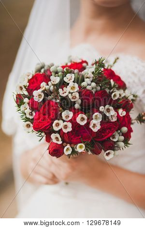 Beautiful Wedding Bouquet Of Red Roses Flowers In Hands Of Anonymous Young Bride