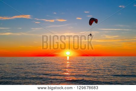 Silhouette of paraglider flying over sea at sunset