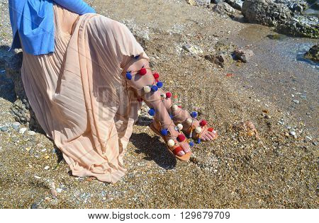 woman advertises traditional greek sandals gladiator on beach