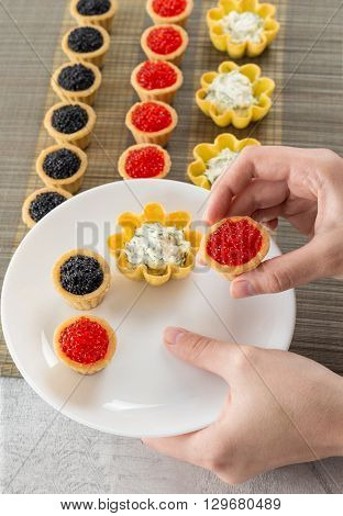 Tartlets filled with cheese and dill salad and caviar on bamboo placemat and a hand choosing tartlets to plate top view