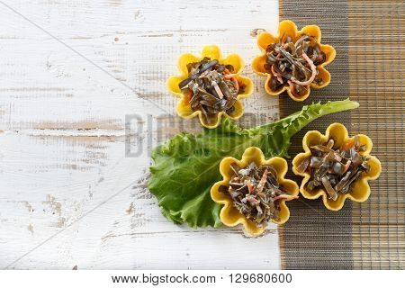 Tartlets filled with seaweed salad on bamboo placemat against rustic wooden background horizontal top view with copy space