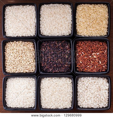 Various types of rice in black bowls on wooden table