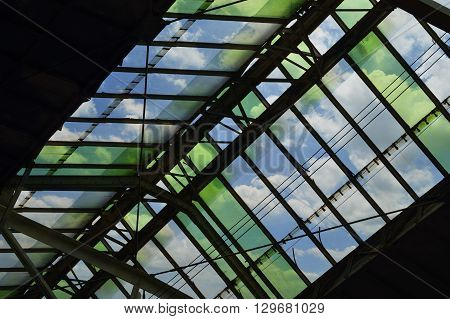 Green glass roof detail of train station over blue sky Bangkok Thailand