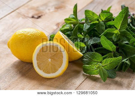 fresh mint leaves and lemon lies on a wooden background. lemon and mint for dessert and drinks food