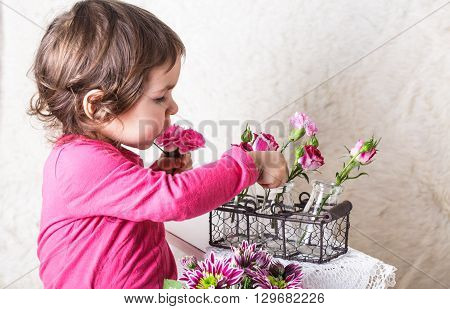 Little girl is smelling the roses. Playing the florist profession