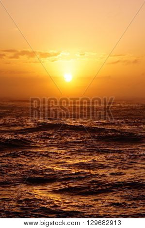 Beautiful Sunset over the ocean with waves moving to shore on the North Shore of Oahu.