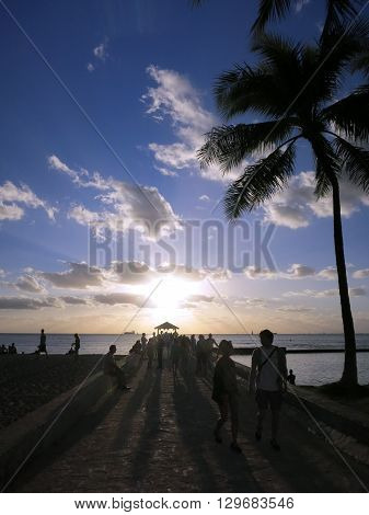 WAIKIKI - FEBRUARY 7: People walk out to Pier to watch Sunset in Waikiki with boats on the water on February 7 2016.