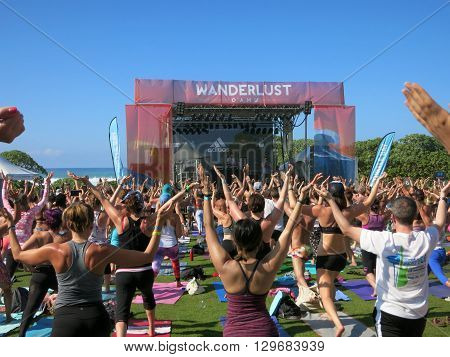 NORTH SHORE HAWAII - FEBRUARY 28: People do Warrior One at Wanderlust MC Yogi Yoga Class at outdoor yoga class facing stage at Wanderlust yoga event on the North Shore Hawaii on February 28 2016.