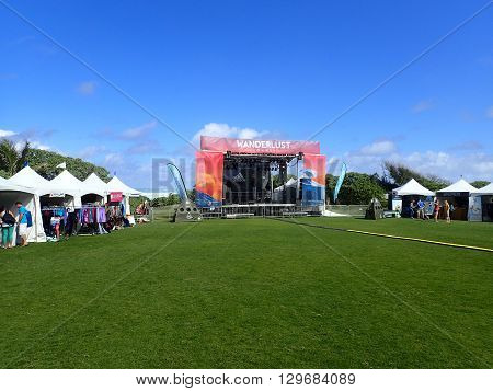 NORTH SHORE OAHU - FEBRUARY 25: Wanderlust O'ahu festival stage and booths against a blue sky and ocean on the North Shore of Oahu Hawaii. February 25 2016.