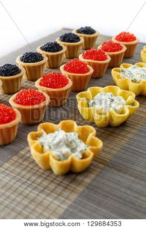 Tartlets filled with cheese and dill salad and caviar on bamboo placemat close up