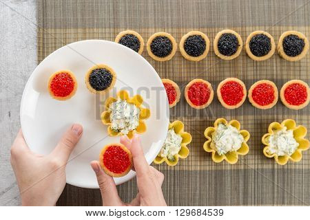 Tartlets filled with cheese and dill salad and caviar on bamboo placemat and a hand choosing tartlets to plate horizontal top view