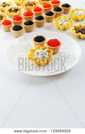 Tartlets filled with cheese and dill salad and caviar and plate with tartlets against white background close up with copy space
