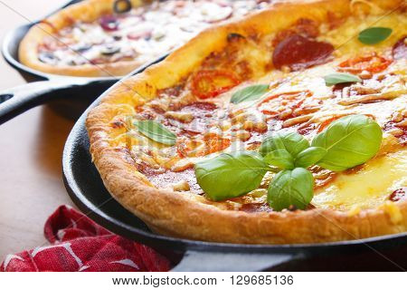 Cast iron skillet pan pizzas on wooden tabble closeup
