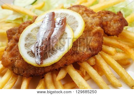 Scandinavian style wiener schnitzel closeup served with lomon slices and anchovies with french fries