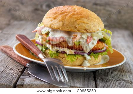 Salmon and shrimp burger mayonnaise on bottom bun breaded salmon shrimp patty and tartar sauce with fresh shrimps on gray wooden boards background