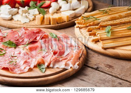 Italian appetizer - various types of ham, cheese and grissini