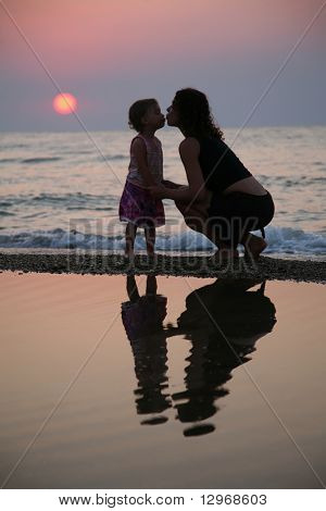 Mother with daughter ashore on sunset