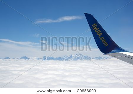 GENEVE AIRPORT SWITZERLAND ALPES - APRIL 28 2015: An Aircraft operated by UIA (Ukraine International Airlines) flying between Alpes mountains before landing in Geneve airport